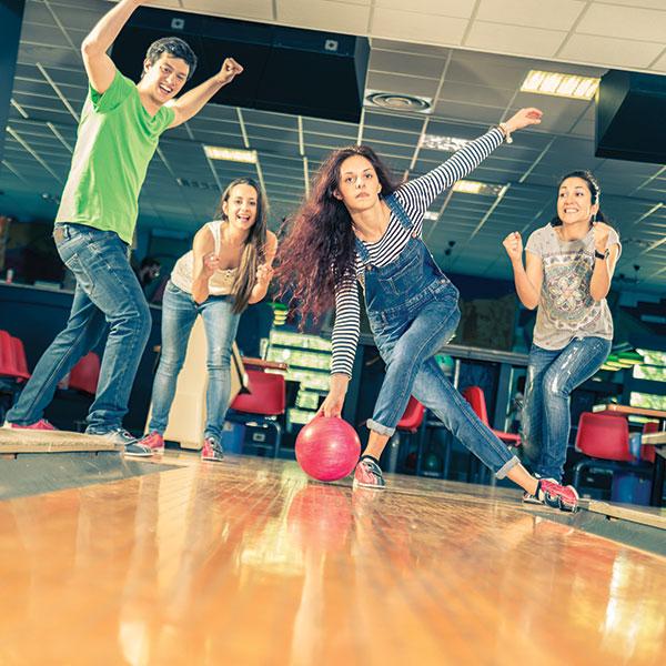 Teens having fun while bowling