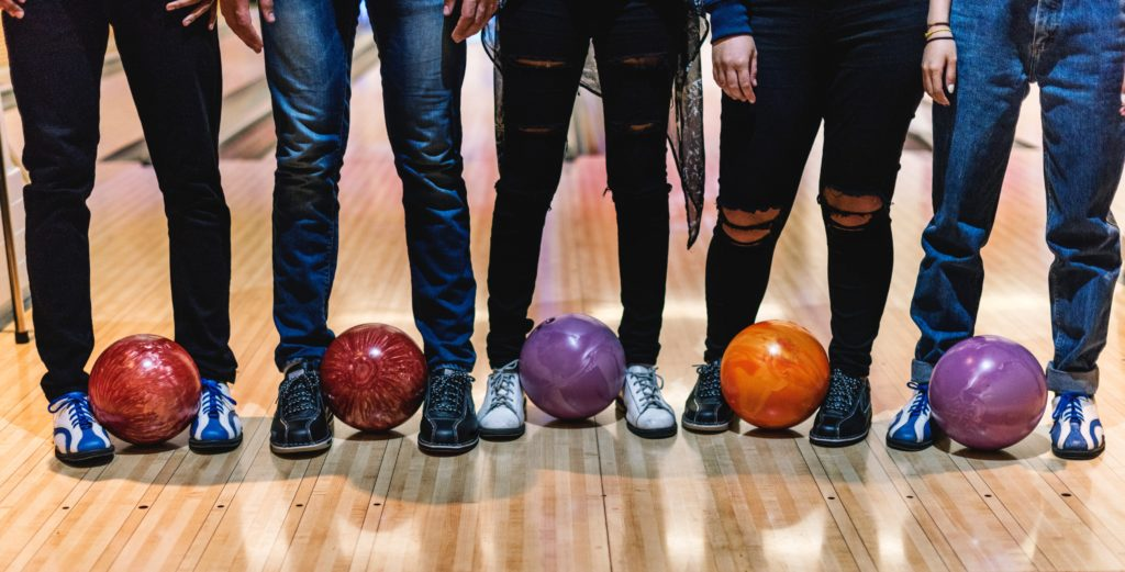 Waist down shot of people standing with bowling balls at feet