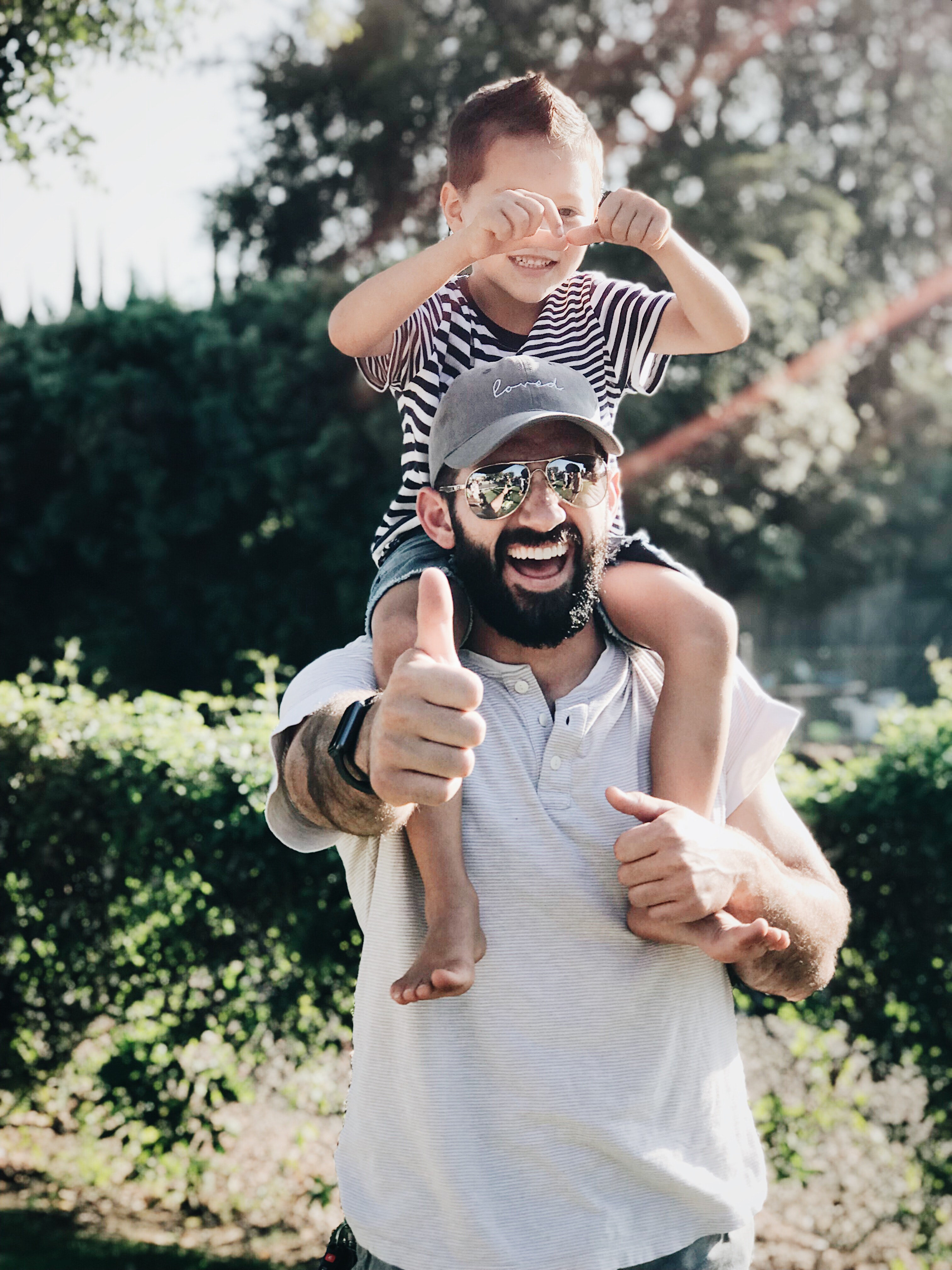 Happy kid riding father's shoulders while dad smiles at camera