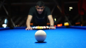 Closeup of billiard ball with man in background