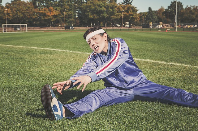 Woman in track suit stretching on grass field
