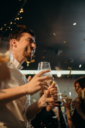 Smiling man holding wine glass in party atmosphere