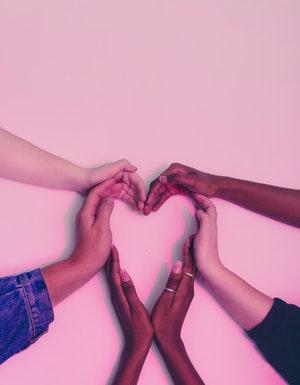Several hands forming heart shape against pink background