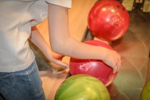 Close up photo of person picking up a bowling ball from the ball return