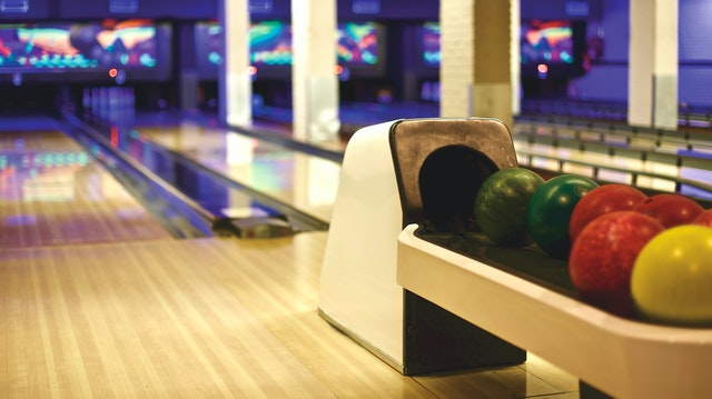 Photo of bowling ball return in front of bowling alley lanes and pins