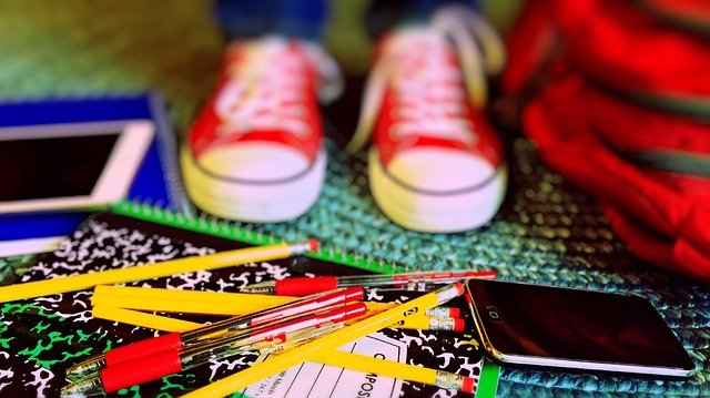 Kid standing by school supplies