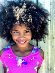 Cute girl with curly natural hair smiling at camera