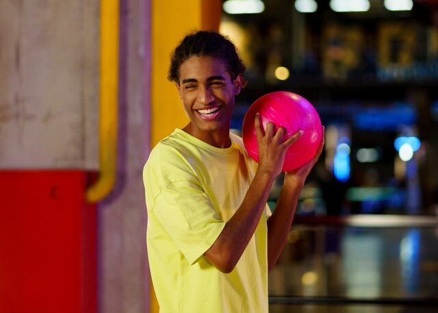 Happy young man holding a bowling ball