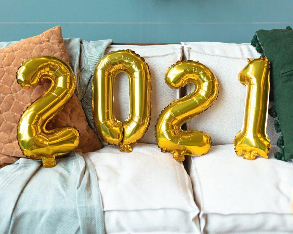 Gold 2021 balloons on white sofa