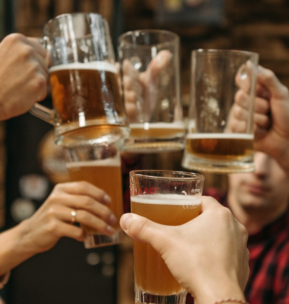 close up photo of friends toasting pint glasses of draft beer