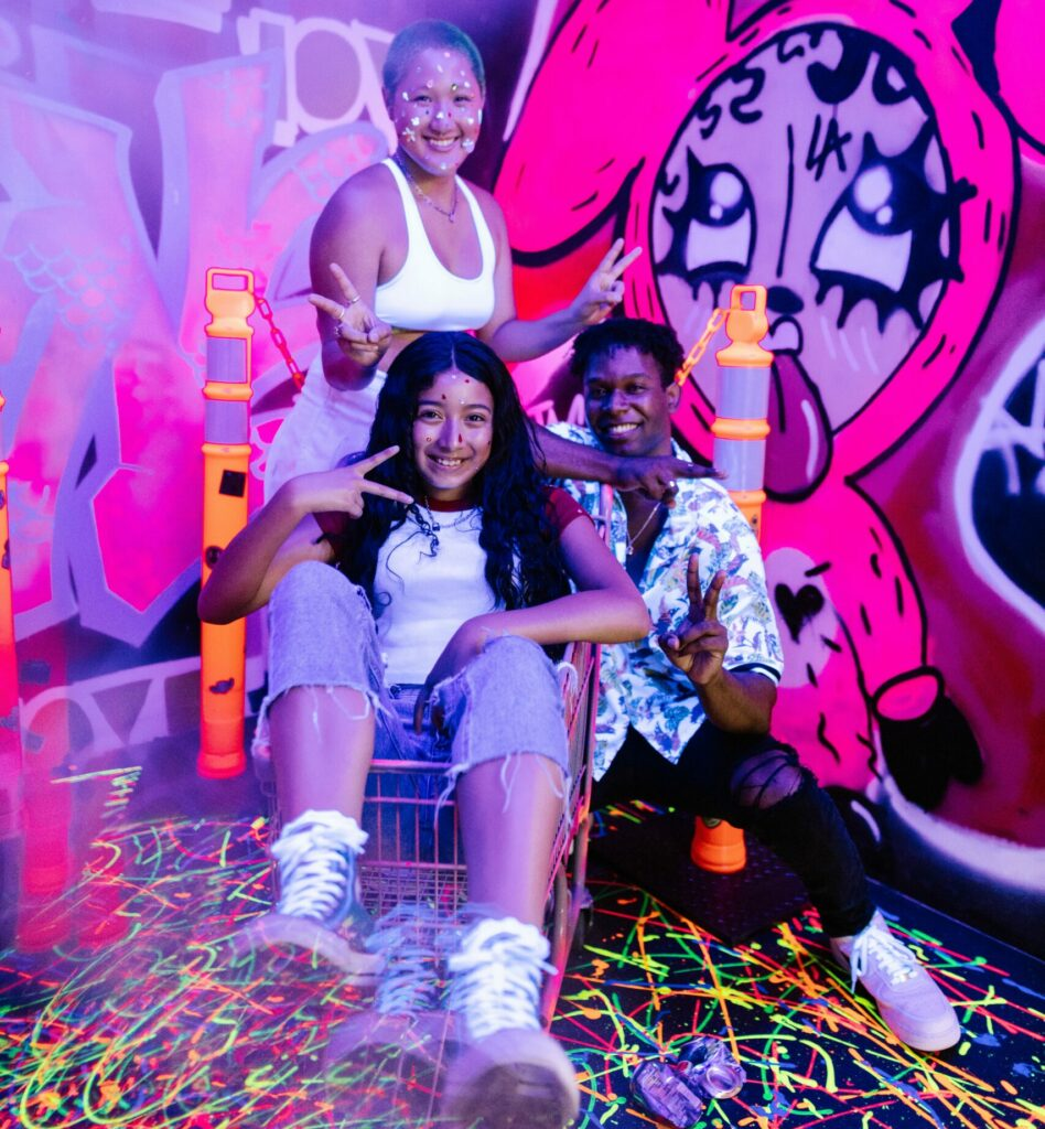 3 teens in black light room with colorful graffiti