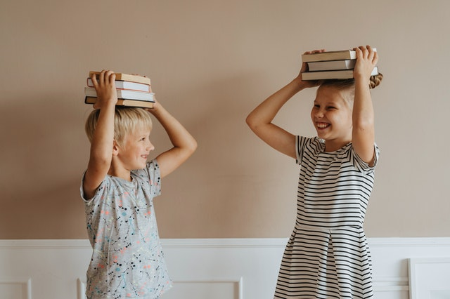 Laughing kids holding stacks of school books on their heads